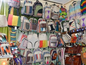Rows of colourful hemp backpacks hanging on a display wall in a shop