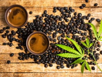 Coffee beans and cannabis leaves arranged on a wooden table